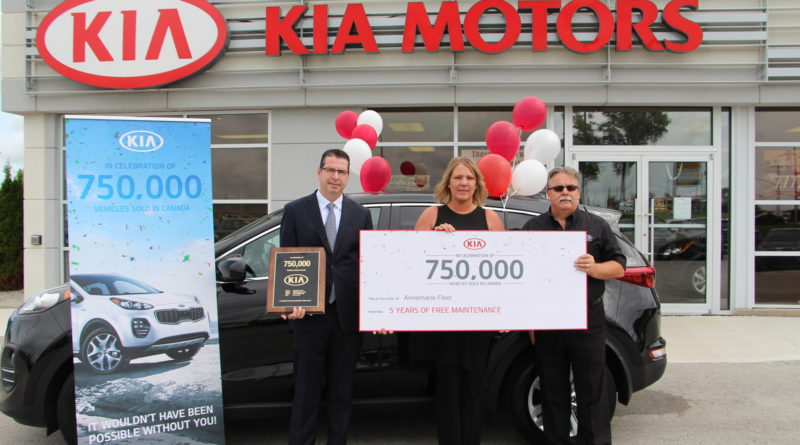 Kia Canada's Ted Lancaster (left) presents happy Sportage buyers with a cheque for 5 year's free maintenance