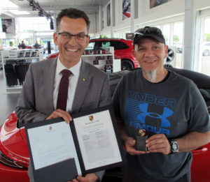 Porsche Canada president and CEO, Alexander Pollich, left, is shown presenting a letter of authenticity and a keepsake to Rob Tenuta, certifying he is the owner of the 999,999th 911 model ever built, a 2017 Carrera 4 Targa GTS.
