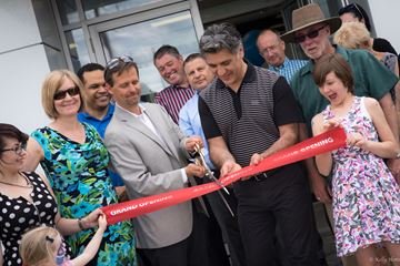 Dealer Mitch Coutu (left) and Mayor Louis Antonakos cut the ribbon to open March Ford.